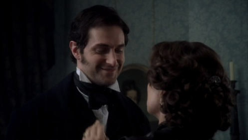 Mrs. Thornton (Sinead Cusack) straights Mr. Thornton's (Richard Armitage) tie in episode 1 of North & South. Source: RichardArmitageNet.com