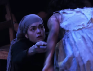 Abigail Williams (Samantha Colley) tells Betty Parris (Marama Corlett) what she must not confess, in Act One of The Crucible. Source: screencap of DigitalTheatre vid.