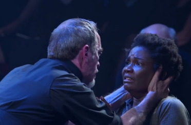 Reverend Hale (Adrian Schiller) convinces Tituba (Sarah Niles) that she can save Salem if she confesses, in Act One of The Crucible. Source: screencap of trailer