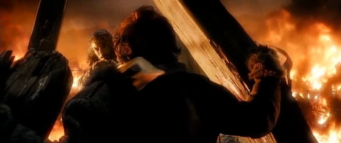 Bard (Luke Evans) aims his arrow at Smaug over the shoulder of his son, Bain (John Bell), in The Hobbit: The Battle of the Five Armies. Screencap.